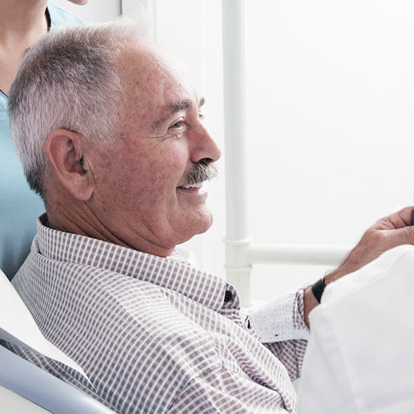 An elderly patient smiling at the Palms dental office while waiting for new dentures