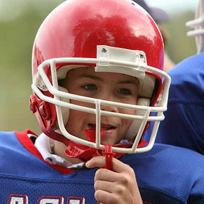 A child wearing an American Football helmet and his preventative dentistry mouthguard