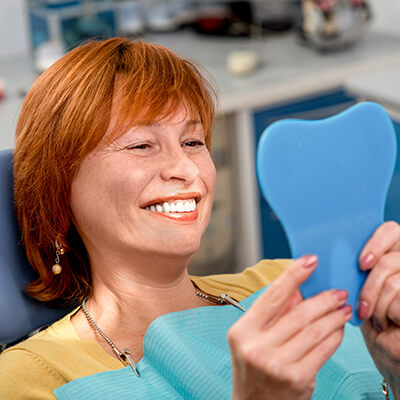 A middle-aged redhead woman looking in a mirror and smiling at the Palms Dentistry office.