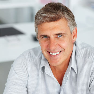 A mature man smiling straight ahead with new dentures courtesy of Palms Dentistry