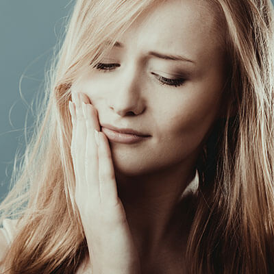A young woman with jaw pain placing her hand on her cheek and looking distressed due to TMJ disorder.