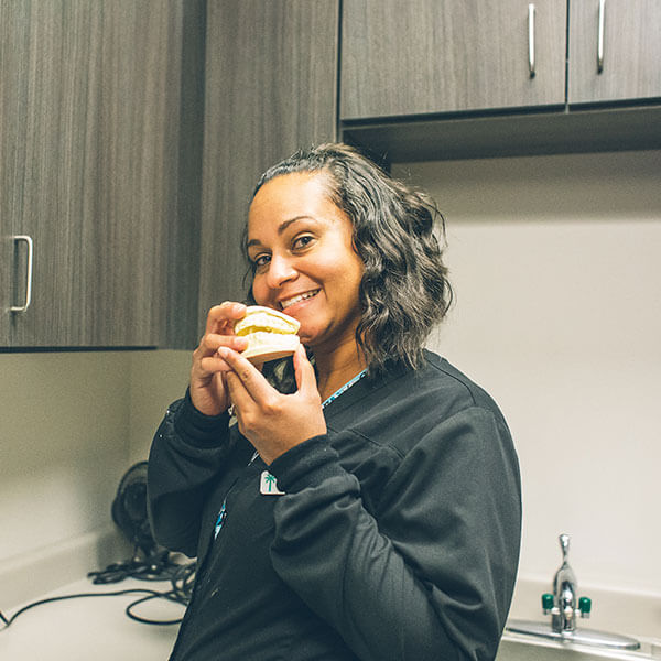 Our assistant, Kalea, in the Palms dental office holding dentures while smiling