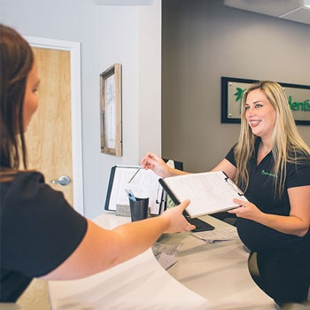 Our Palms Dentistry receptionist delivering a form to one of our new patients
